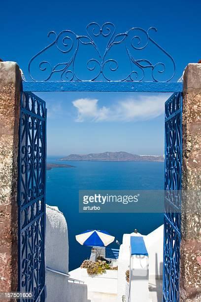 Photo of the ocean through a blue gate