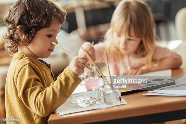 Photo of two children painting with water colors