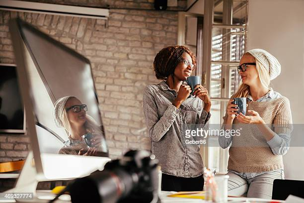 Photo of two female freelance designers having coffee