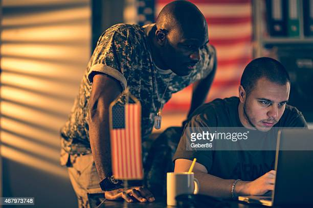 Photo of two young american soldiers looking at laptop