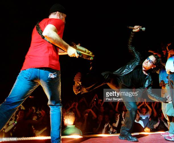 ARNHEM Photo of U2 and THE EDGE and BONO Bono The Edge performing live onstage on Elevation tour Bono kicking at The Edge's guitar with crowds...