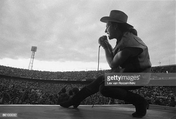 ROTTERDAM Photo of U2 Bono performing live onstage at De Kuip stadium on The Joshua Tree tour from stage showing crowds of fans in stadium