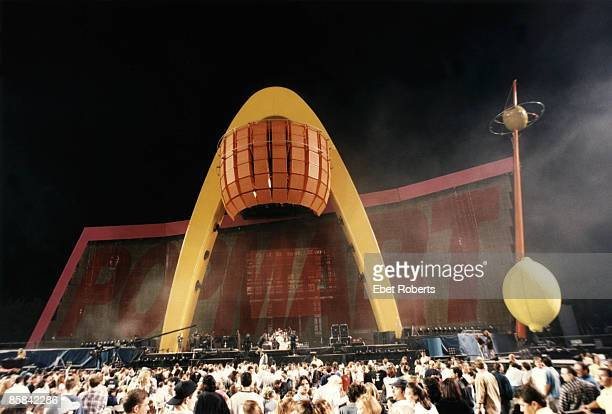 Photo of U2 Group performing on stage PopMart tour showing stage set and speakers