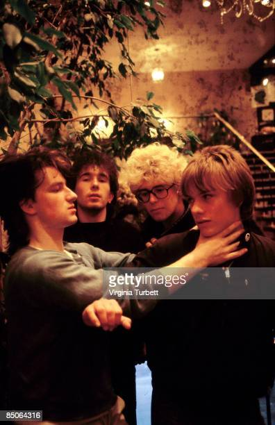 BELGIUM Photo of U2 LR Bono The Edge Adam Clayton Larry Mullen Jnr Bono miming strangling Larry Mullen posed group shot