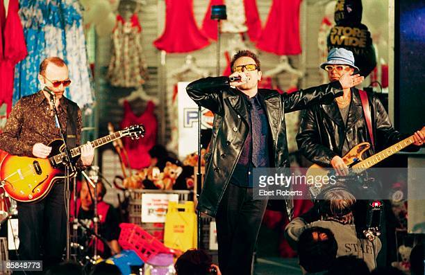 Photo of U2 LR The Edge Bono Adam Clayton performing live at promotional show in Greenwich Village KMart shop lingerie dept to promote PopMart tour