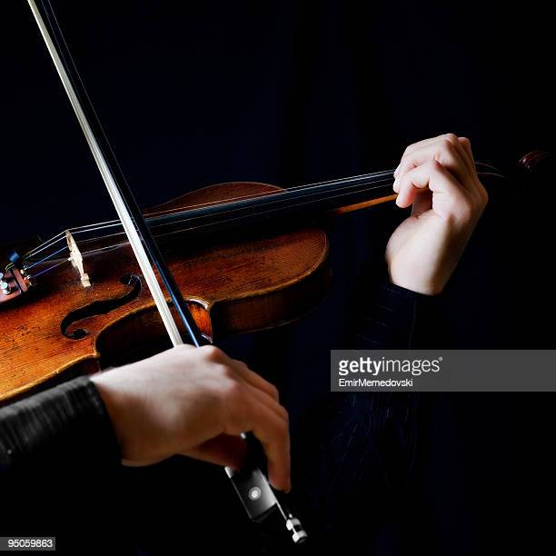 Photo of violin player on black background