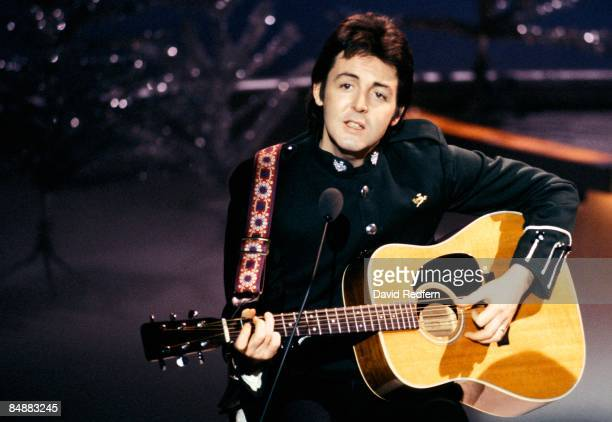 CENTRE Photo of WINGS and Paul McCARTNEY in Wings performing on TV show playing acoustic guitar on Mike Yarwood Christmas Special