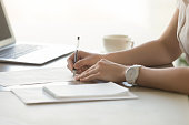 Close up photo of womans hands with pen signs contract. Businesswoman puts her personal signature on business agreement. Female entrepreneur working with business documents. Paperwork in office