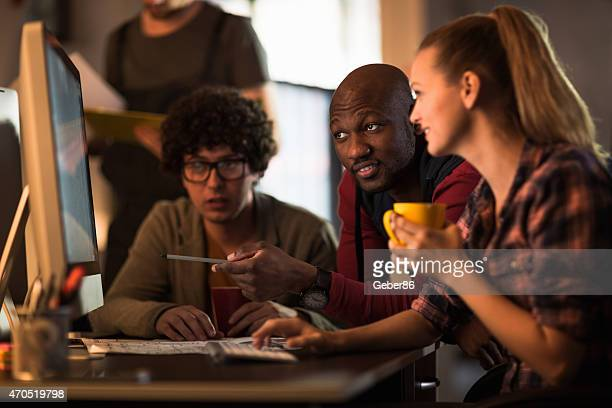 Photo of young freelance designers working late in office