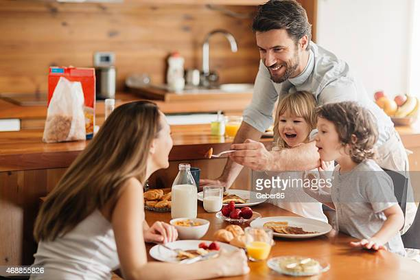 Photo of young happy family having their breakfast