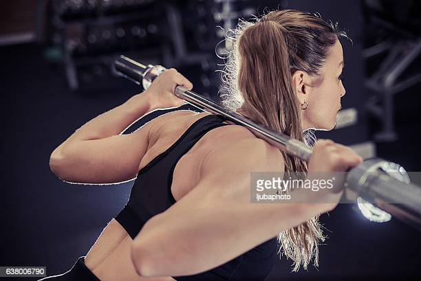 Photo of young woman with barbell flexing muscles in gym
