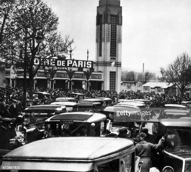 Photo prise dans les années 30 de voitures stationnant devant l'entrée de la Foire de Paris qui se tient au parc des expositions de la Porte de...
