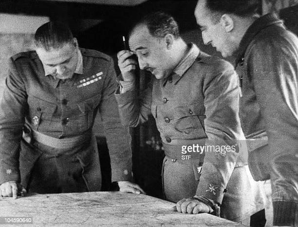 Photo prise durant la guerre civile espagnole après 1936 du général Franco surpervisant les opérations militaires à l'aide d'une carte entouré de son...
