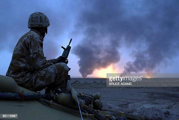 Photo released 23 March 2003 shows a British soldier watching 20 March 2003 oil wells on fire in Southern Iraq AFP PHOTO POOL/BRUCE ADAMS