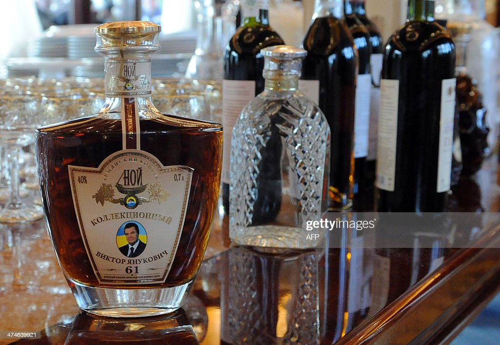 Photo shows a bottle of brandy featuring a photo of ousted Ukrainian President Viktor Yanukovych at the Mezhyhirya, his former residence, near Kiev on February 24, 2014. Ukraine issued an arrest warrant on February 24 for ousted president Viktor Yanukovych over the 'mass murder' of protesters and appealed for $35 billion in Western aid to pull the crisis-hit country from the brink of economic collapse. The dramatic announcements by the ex-Soviet nation's new Western-leaning team -- approved by parliament over a chaotic weekend that saw the pro-Russian leader go into hiding -- came as a top EU envoy arrived in Kiev to buttress its sudden tilt away from Moscow.
