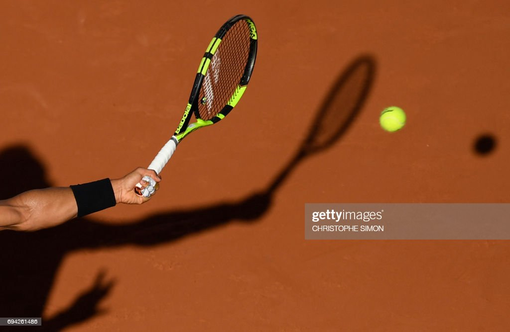 TOPSHOT - Photo shows a close up of the racket and shadow of Spain's Rafael Nadal hiting a return to Austria's Dominic Thiem during their semifinal tennis match at the Roland Garros 2017 French Open on June 9, 2017 in Paris. /