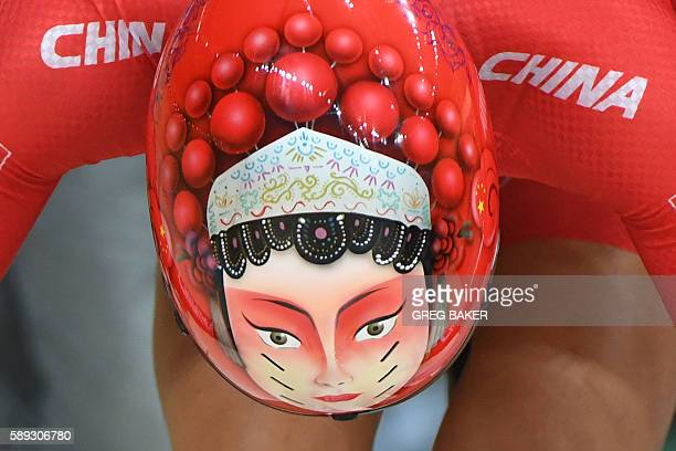 A photo shows a face painted onto the helmet of China's Zhong Tianshi as she lines up on the track before the women's Keirin second round track...