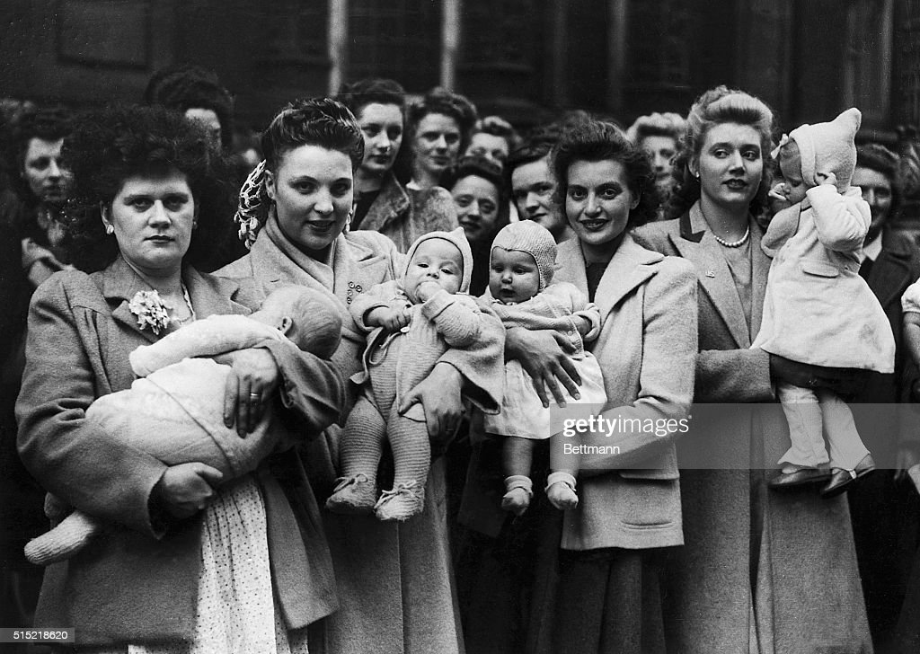 Photo shows a group of GI wives with their children waiting in the queue to get into Caxton Hall for the protest meeting tonight L to r Mrs H...