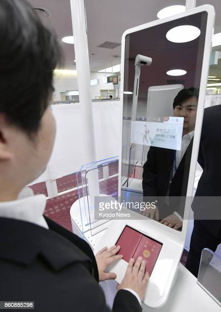 Photo shows a man demonstrating a facial recognition machine which is part of the new immigration control system at Haneda airport in Tokyo on Oct 13...