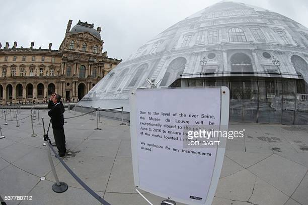 A photo shows a placard announcing the closure of the Louvre Museum on June 3 2016 in Paris after the rainswollen river Seine reached its highest...