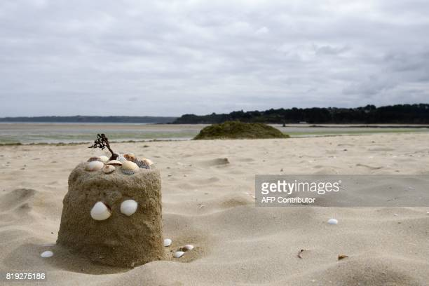 A photo shows a sand castle with seashells next to a pile of green algae on a beach in Locquirec western France on July 2 2017 Tides of green algae...