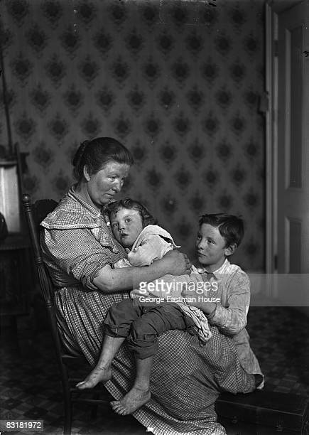 Photo shows an immigrant mother holding her two children as she sits inside a tenement apartment in the lower east side of New York City New York 1905