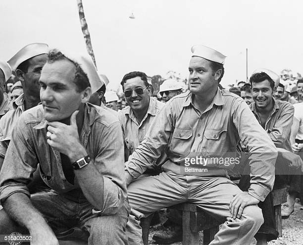 Photo shows comedian Bob Hope wearing a Naval uniform sitting on a bench among an audience of amused sailors