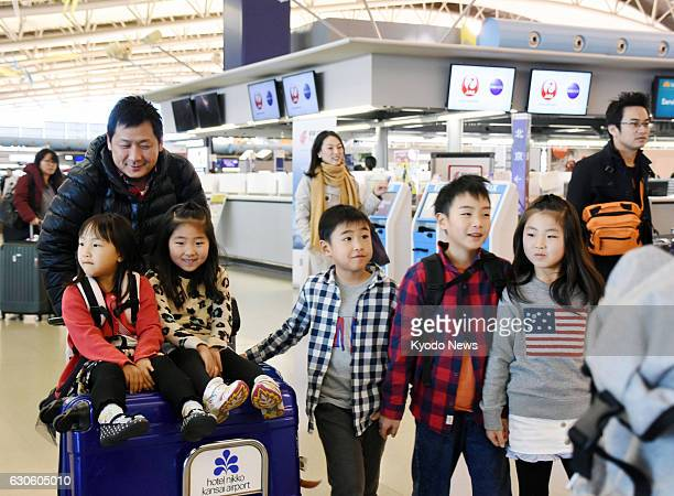 Photo shows families heading for their flights at Kansai International Airport in Osaka Prefecture on Dec 28 for their New Year's holidays