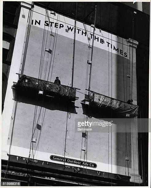 Photo shows sign painters work hoists painting on a large building Undated