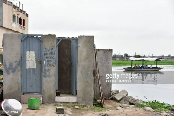 A photo shows toilets reading 'Please come in with water' in an impoverished neighbourhood of Abidjan on November 14 2017 / AFP PHOTO / ISSOUF SANOGO