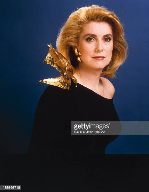 Photo Studio Of Catherine Deneuve Photo studio plan de face souriant de Catherine DENEUVE vêtue d'une robe d'Yves SAINT LAURENT avec un oiseau de...
