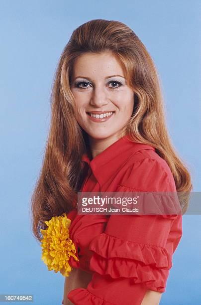plan de face souriant de SHEILA portant une chemise brassière à manches volantées une fleur jaune entre les seins