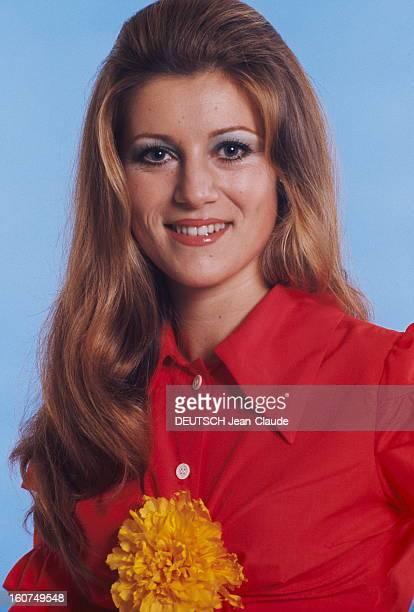 plan de face souriant de SHEILA portant une chemise brassière rouge une fleur jaune entre les seins