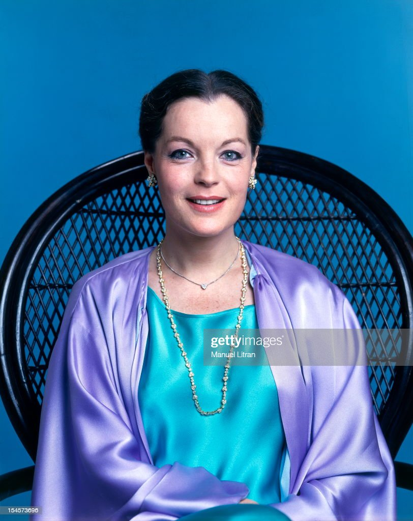 Photo studio Romy Schneider on the occasion of his 40th birthday: plan smiling face of the actress in turquoise blue dress in a purple shawl and Yves Saint Laurent dress with a Van Cleef amp; Arpels, sitting in a chair.