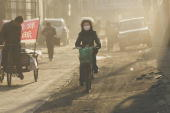 Photo taken 15 February 2007 shows a woman wearing a mask against pollution on a bicycle in the city of Linfen in China's Shangxi province which has...