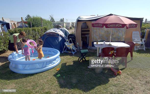 A photo taken 18 July 2006 showing children playing in a backyard wadingpool near their caravan at the camping 'Le point du jour' in...