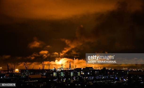 A photo taken at night on July 29 2017 shows flames and smoke rising above the Shell refinery in Rotterdam A fire broke out on the night of July 29...