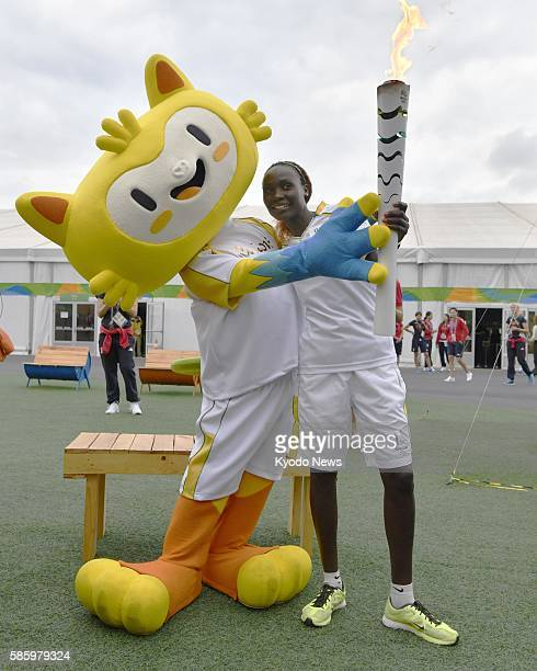 Photo taken Aug 4 at the athletes village for the Rio de Janeiro Olympics shows a torchbearer and the Olympic Games official mascot Vinicius The...