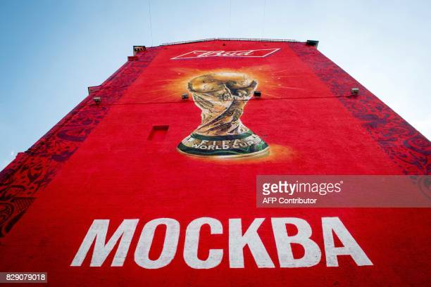 A photo taken August 10 2017 in downtown Moscow shows an advert for a nonalcoholic beer painted on a wall featuring the FIFA World Cup and reading...