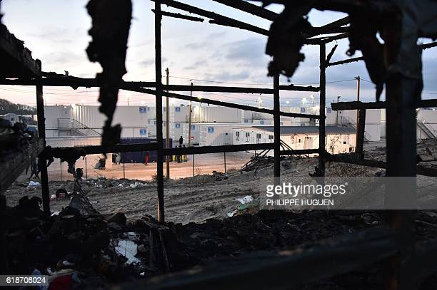 A photo taken early on October 28 2016 shows a burntout structure with housing containers in the background at the 'Jungle' migrant camp in Calais...