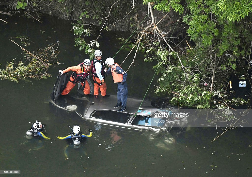 Photo taken from a Kyodo News helicopter on May 29, 2016, shows investigators examining a sunken van in a dam reservoir in Osaka, western Japan. Five men were confirmed dead and another was in critical condition after the van plunged into the reservoir from a road about 10 meters above, with local police and firefighters suspecting driver error caused the accident.