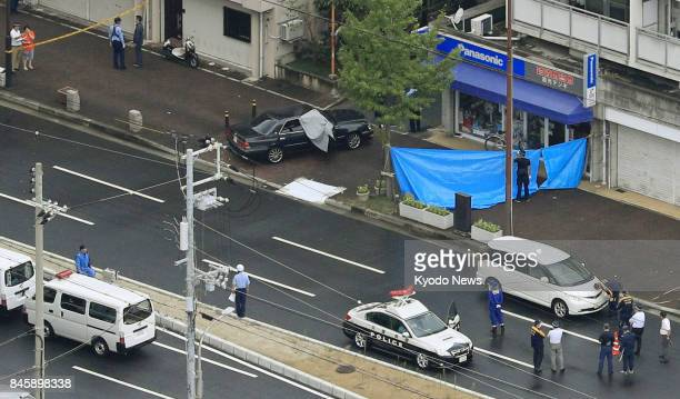 Photo taken from a Kyodo News helicopter on Sept 12 shows Hyogo prefectural police working in a residential area of Kobe where a man believed to be a...