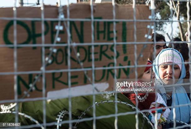 A photo taken from the Macedonian side of the border shows a woman holding her child next to a placard reading 'open the borders no return' as...