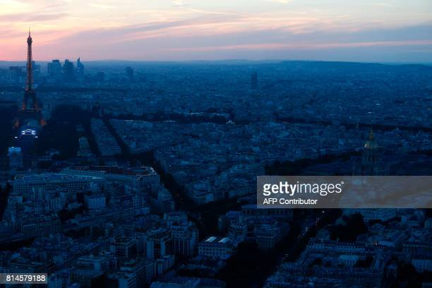 A photo taken from the Panoramic Observatory of the Montparnasse Tower shows the Eiffel Tower and Hotel des Invalides during sunset on July 14 2017...