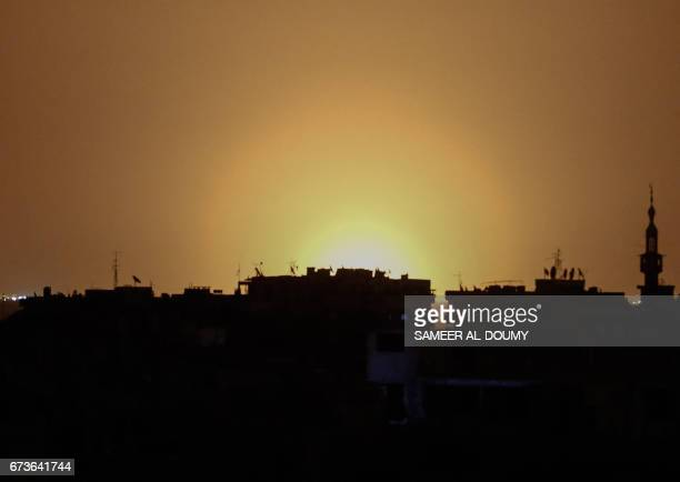 TOPSHOT A photo taken from the rebelheld town of Douma shows flames rising in the distance which are believed to be coming from Damascus...