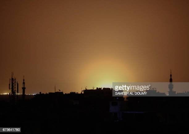 A photo taken from the rebelheld town of Douma shows flames rising in the distance which are believed to be coming from Damascus International...