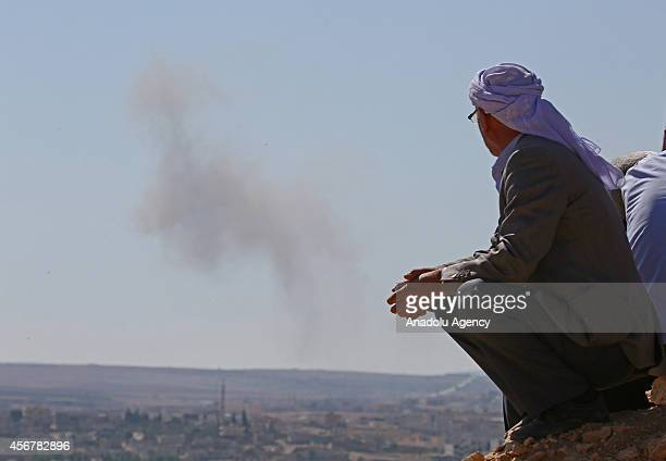 A photo taken from the Suruc district of Sanliurfa Turkey shows a man watching the Ayn alArab city of Syria after the USled coalition bombed the...
