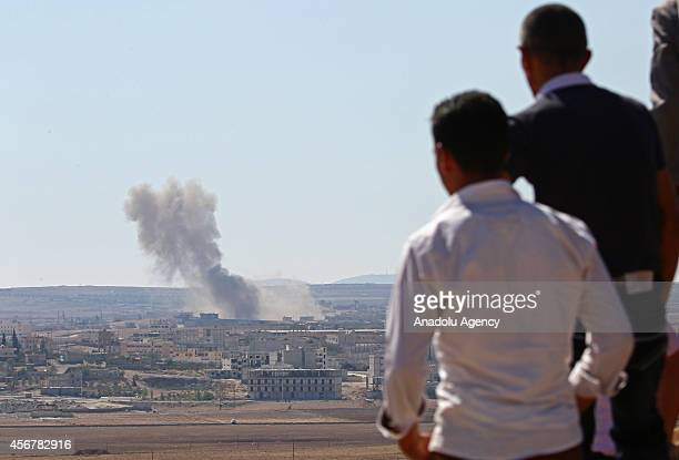 A photo taken from the Suruc district of Sanliurfa Turkey shows men watching the Ayn alArab city of Syria after the USled coalition bombed the...
