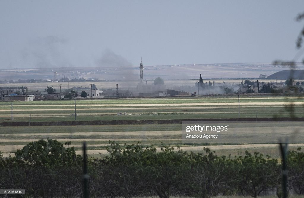 A photo taken from Turkey's Kilis shows that smoke rises over the Duden village of Azaz town of Syria as the clashes between Free Syrian Army and Daesh terrorists continue on May 5, 2016.