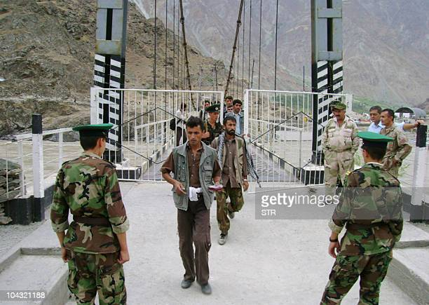 A photo taken in August 2010 and made available on September 21 2010 shows Tajik border guards checking identification documents of people crossing...